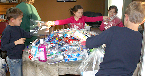 Younger members of the Goff family pitch in as items are sorted and packaged for needy families in East Tennessee. Photo by W. Clay Crook/The Lexington Progress.