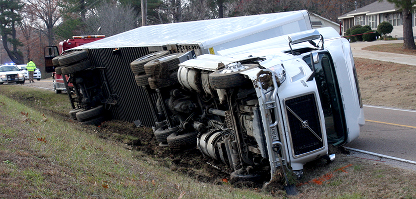 A transfer truck landed on its side after leaving the roadway and falling from the steep bank on Hwy 100, just west of Scotts Hill. Photo by W. Clay Crook/The Lexington Progress.